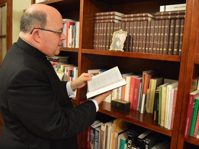 Monseñor Ferrer Grenesche ojea una de las obras que conserva en su biblioteca. / JG